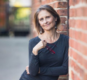 Joyce Griggs standing next brick wall